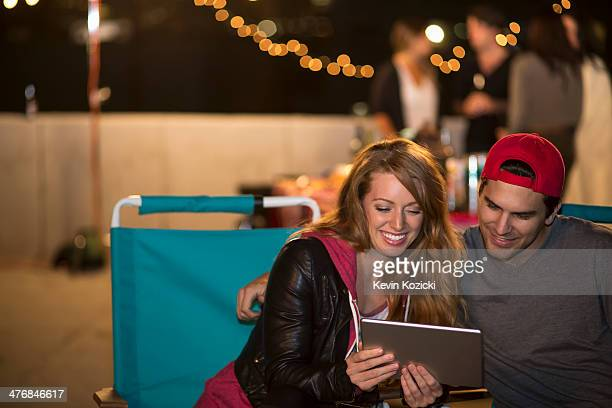 Young couple using digital tablet at rooftop barbecue