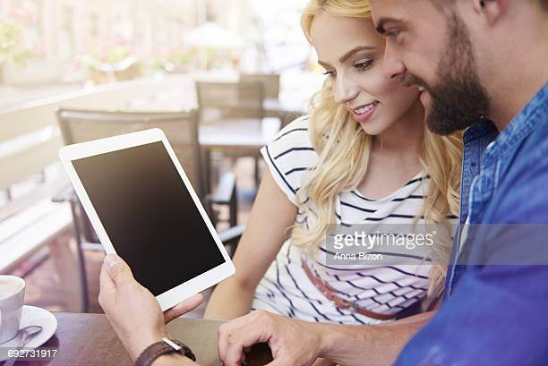 Young couple using digital tablet at the cafe. Sandomierz, Poland.