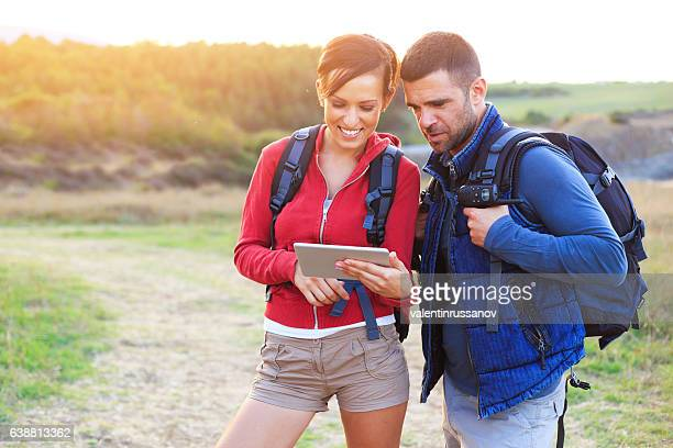 Young couple using digital tablet for navigation in hiking