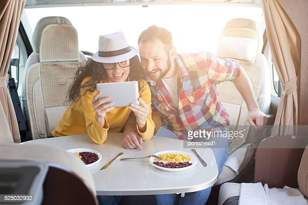 Giovane coppia utilizzando compressa digitale interno del caravan