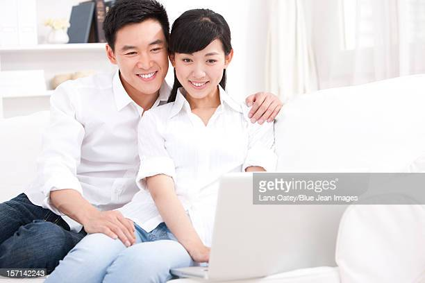 Young couple using laptop in sofa