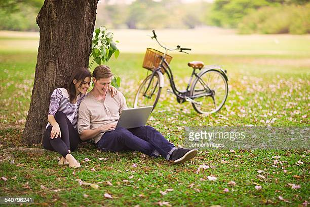 Young couple using laptop outdoor