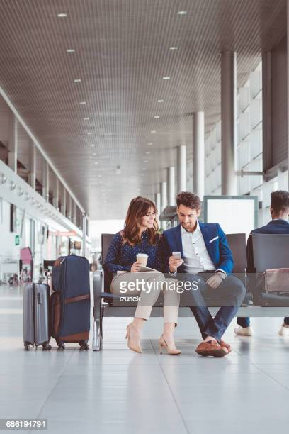 Young couple using mobile phone at the airport