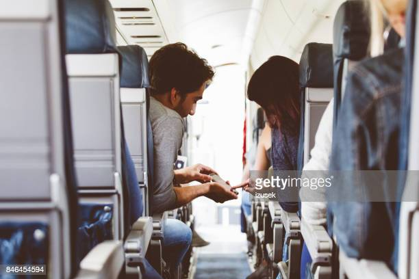 Young couple using mobile phone in the flight
