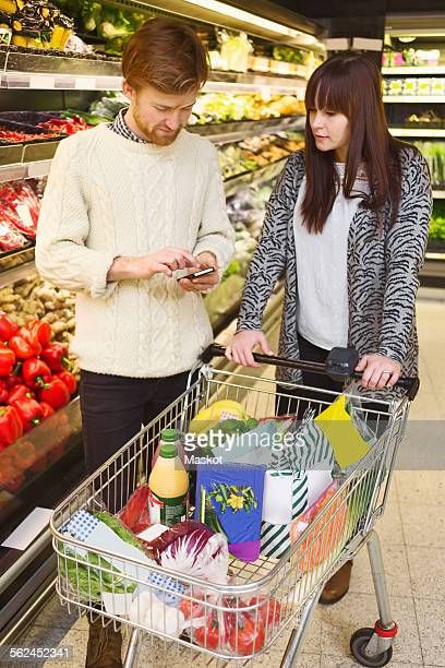 Young couple using mobile phone while buying groceries at supermarket