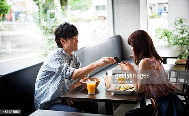 Young couple using smartphone during lunch