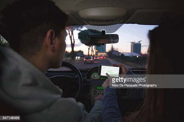 Young couple using smartphone in car