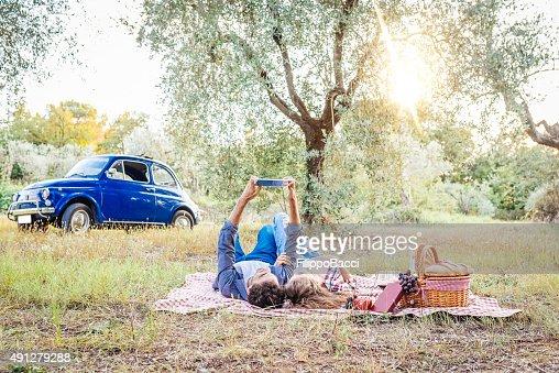 タブレットを使用して若いカップル、屋外でのピクニック