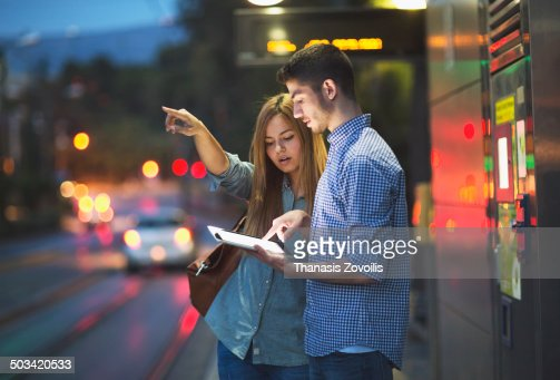 Young couple using tablet on holiday in the night