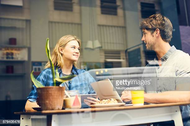 Young couple using technologies through window in cafe