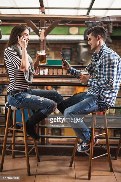 Young couple using wireless technology in a cafe.
