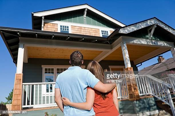 Young couple viewing new home, outdoors