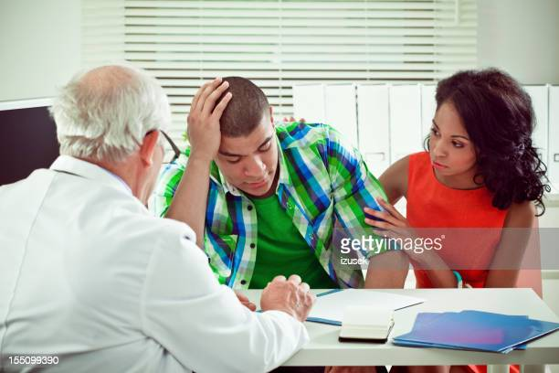 Young couple visiting a senior doctor
