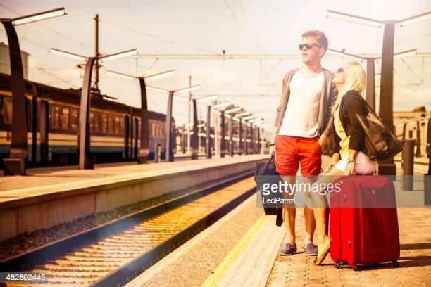 Casal Jovem está à espera de um comboio na plataforma