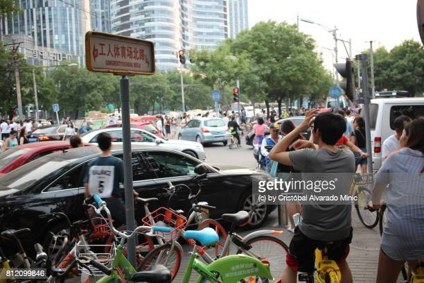 Young Couple Waiting On Public Rental Bicycles In Beijing
