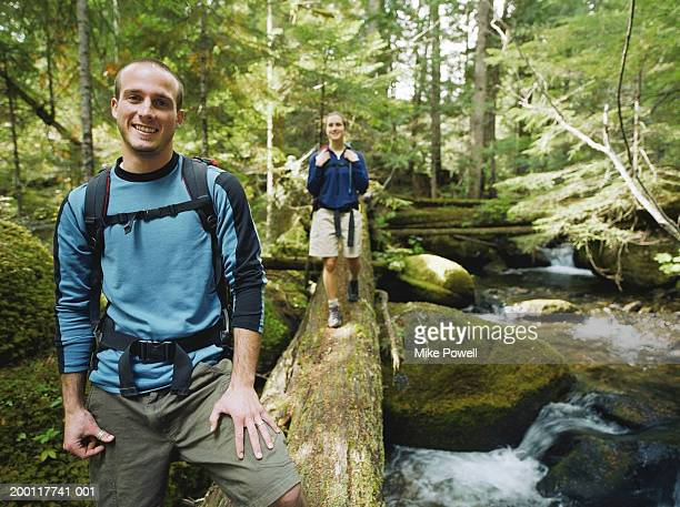 Young couple walking across river on log, Portrait, (focus on man)