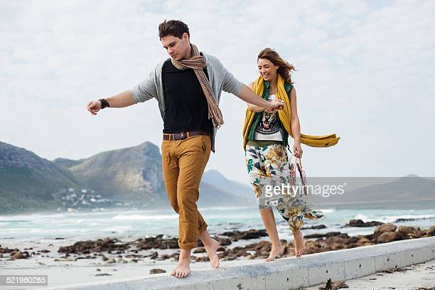 Young couple walking along cement block on beach, Cape Town, Western Cape, South Africa