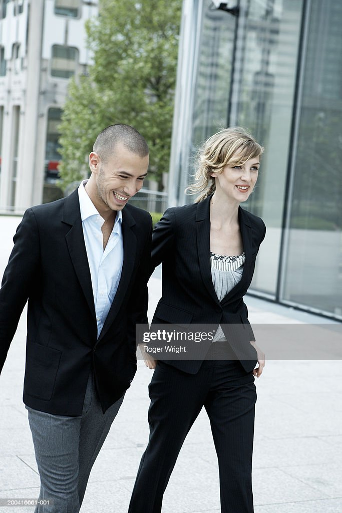 Young couple walking along street, laughing and smiling : Stock Photo