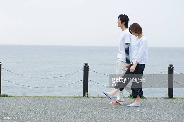 Young couple walking by sea
