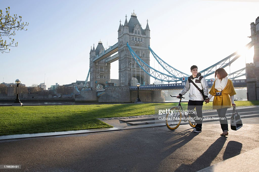 Young couple walking by Tower Bridge, London, England : Stock Photo
