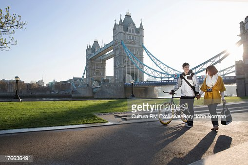 Young couple walking by Tower Bridge, London, England