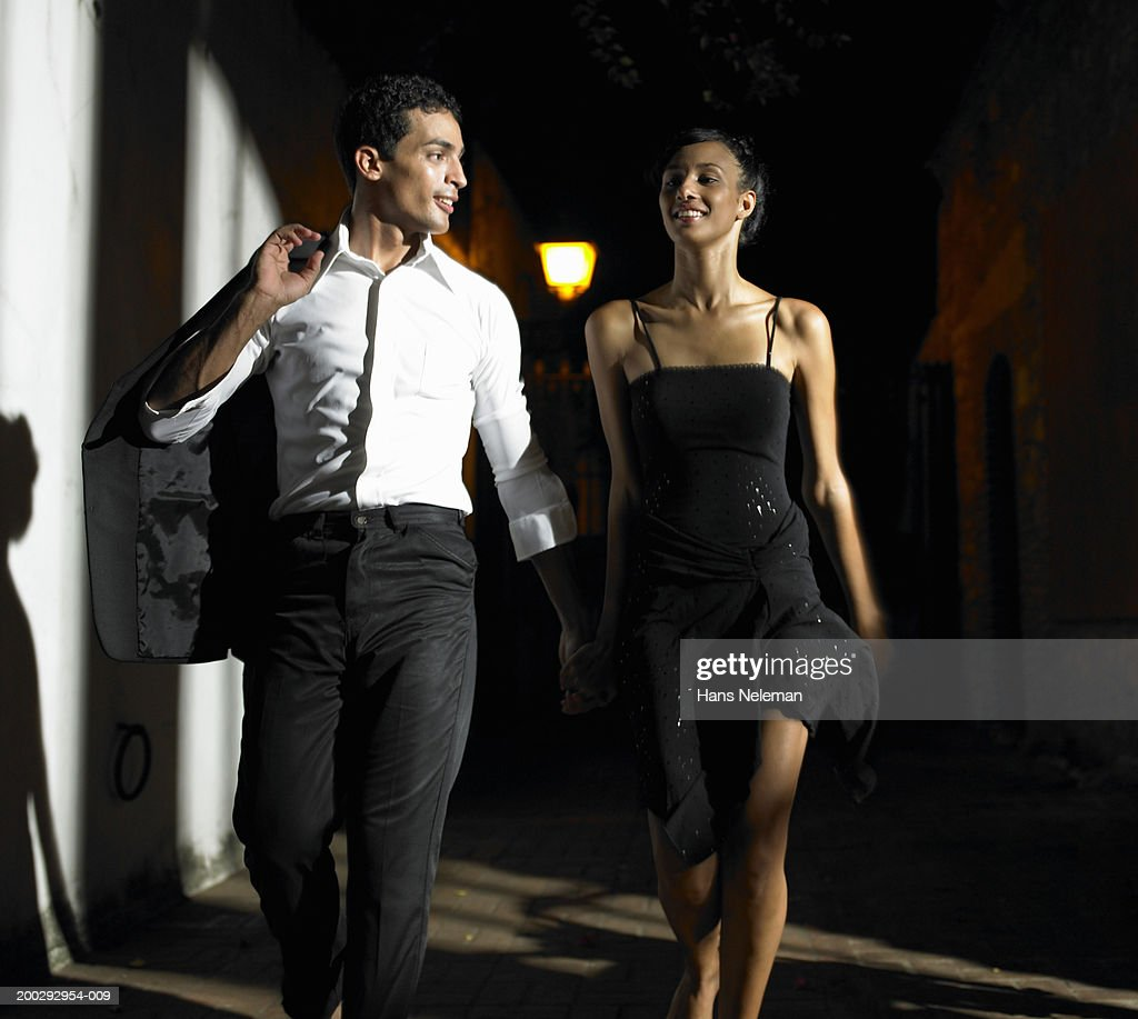Young couple walking down street at night