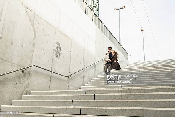 'Young couple walking down the stairs hugging each other, Munich, Bavaria, Germany'
