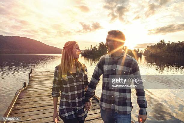 Young couple walking hand to hand on wooden pier