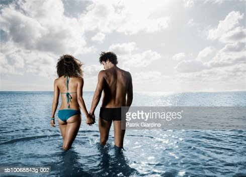 Young couple walking in sea, rear view : Stock Photo