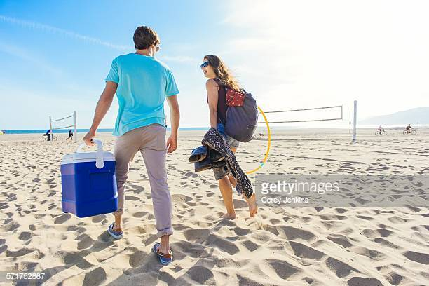 Young couple walking on beach, holding cool box, rear view