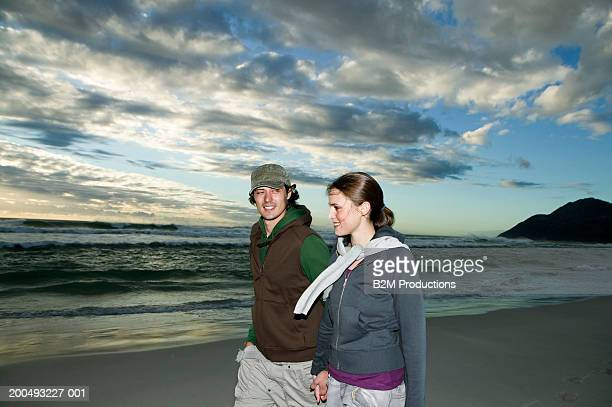 Young couple walking on beach, holding hands, side view