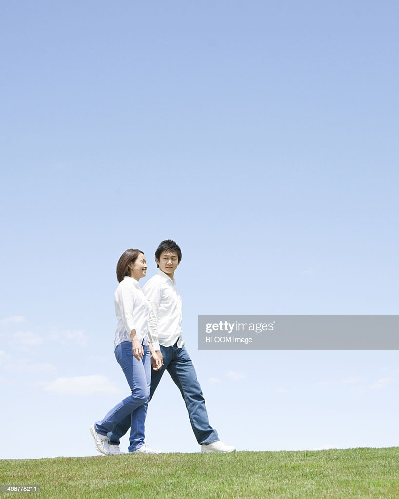 Young Couple Walking On Grassland : Stock Photo