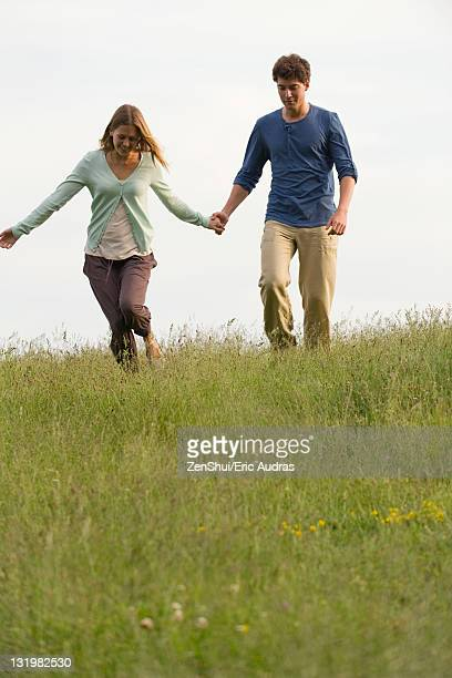 Young couple walking on meadow holding hands