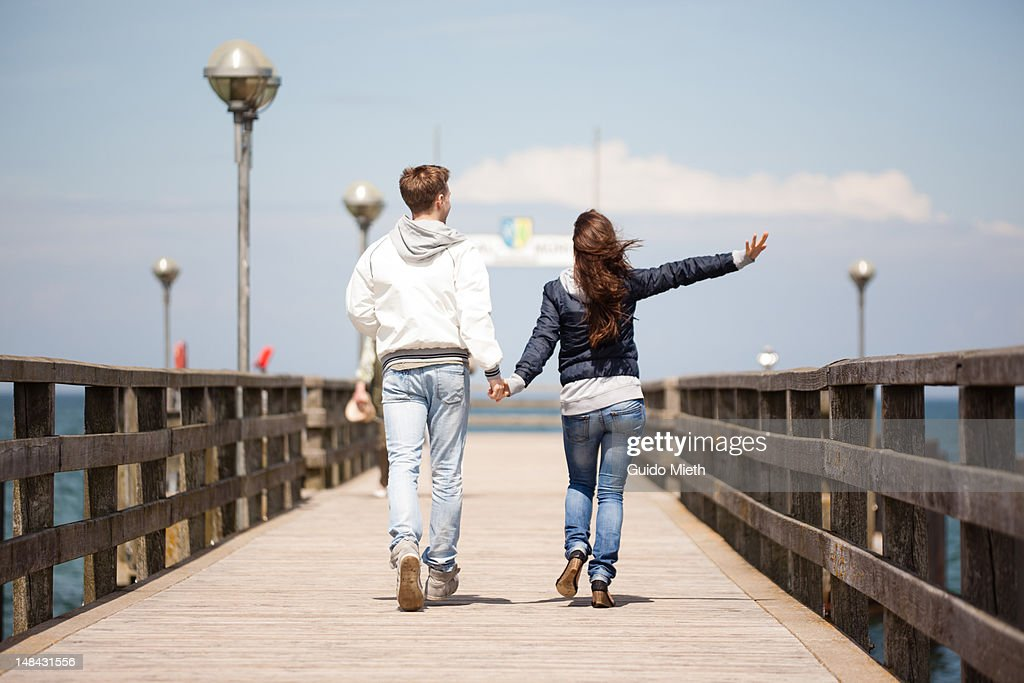 Young couple walking on pier : Stock Photo