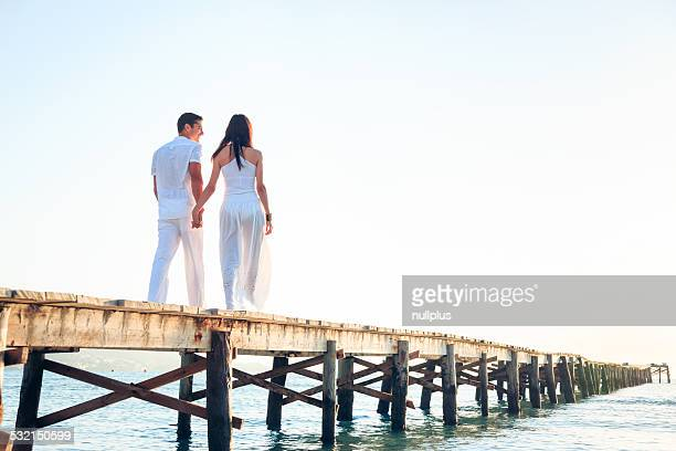 young couple walking on pier