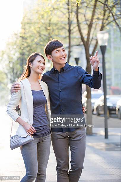 Young couple walking on sidewalk