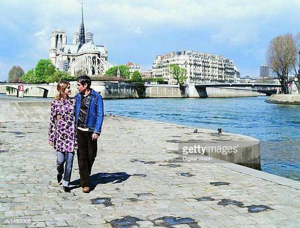 Young Couple Walking on the Left Bank of the River Seine,  Notre Dame in the Background