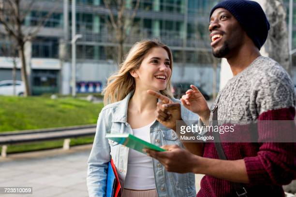 Young couple walking outdoors, holding notebooks, smiling