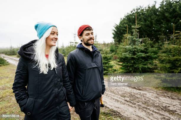 Young Couple Walking Through Pine Forest Looking For Christmas Tree