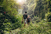 Rear view of young couple walking through woods with their shoes in hand. Man and woman hiking in forest.