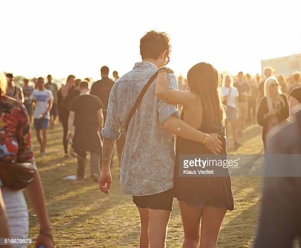 Young couple walking together at big festival