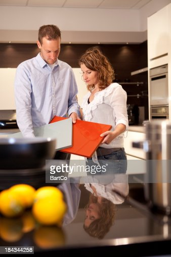 Young couple wants to buy a new kitchen in showroom.