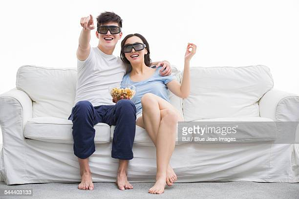 Young couple watching 3D movie in living room