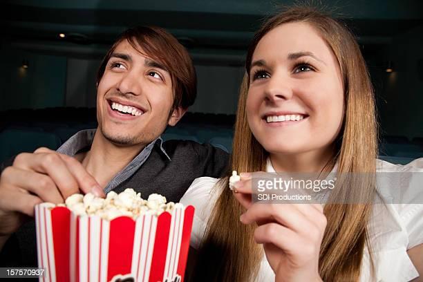 Jeune Couple regarder un film tout en mangeant pop-corn