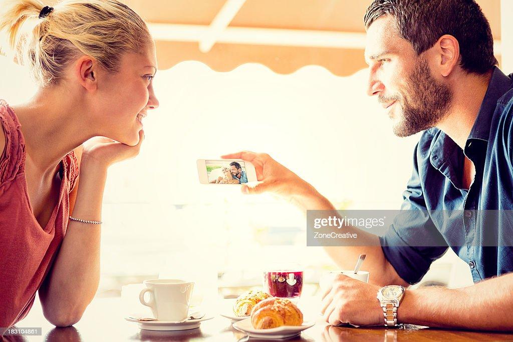 Young couple watching photos at italian café : Stock Photo