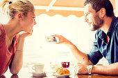 Young couple watching photos at italian café