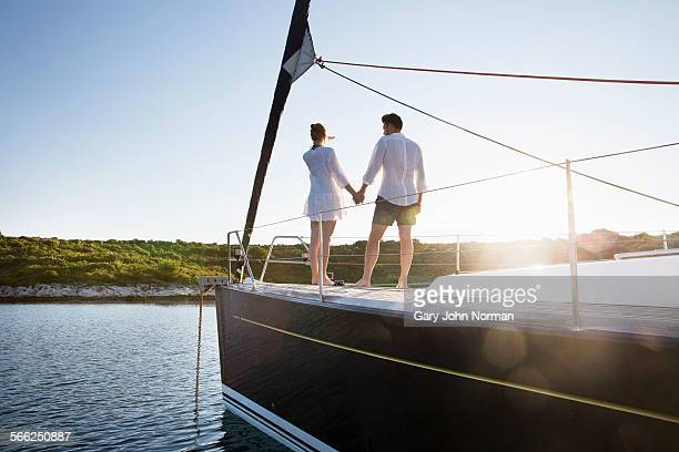 Young couple watching sunrise from bow of yacht.