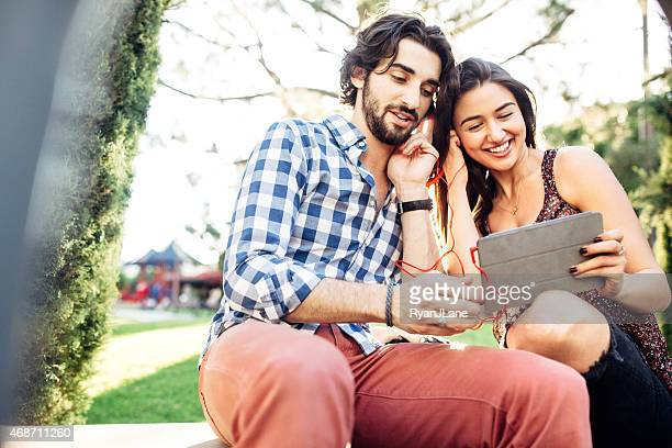 Young Couple Watching Tablet Outdoors