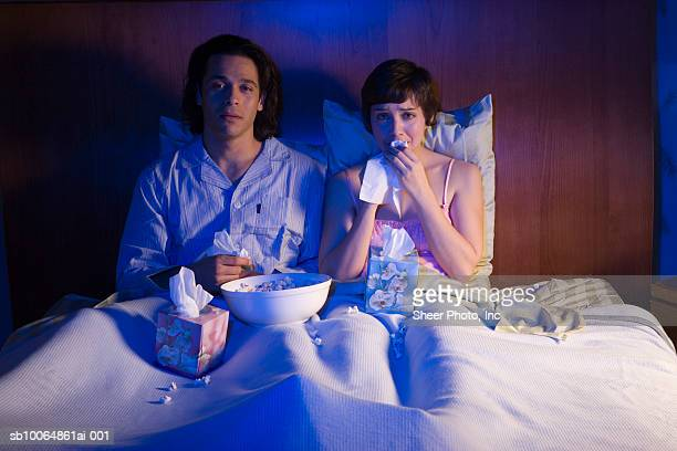 Young couple watching television in bed at night