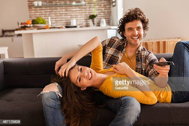 Young couple watching television together
